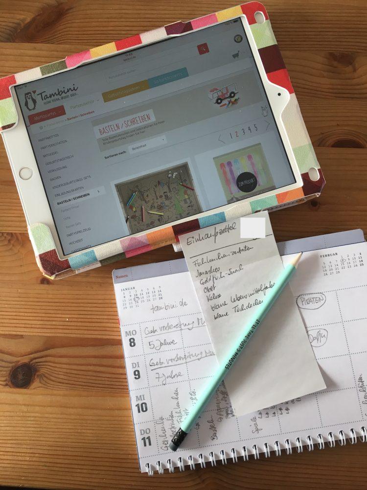 Tablet mit offener Homepage und Notizen zur Geburtstagsplanung