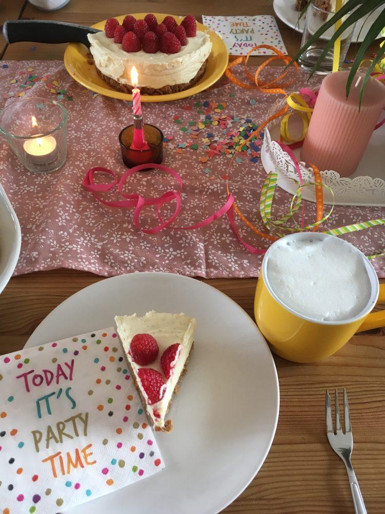 Festlich gedeckter Tisch mit einem Stück Cheesecake auf dem Teller.