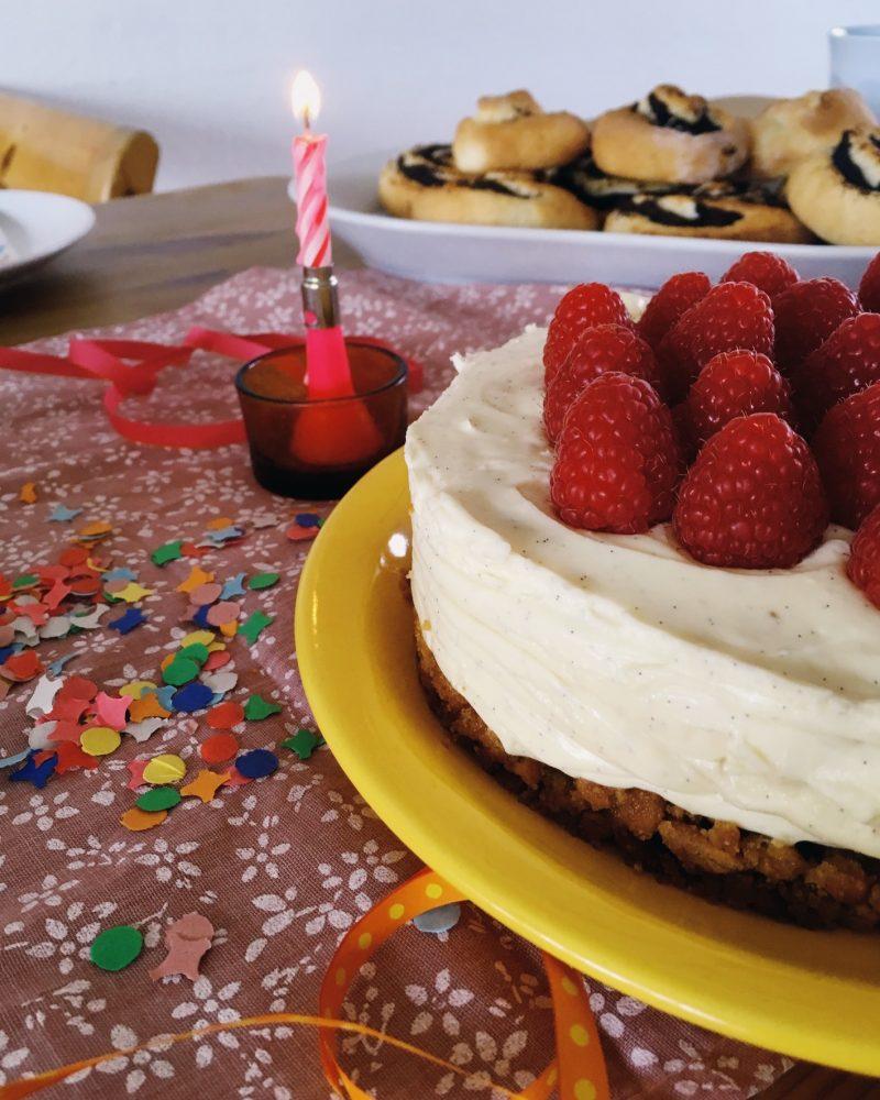Der Cheesecake auf einem festlich gedeckten Tisch von der Seite fotografiert mit den verschiedenen Schichten gut zu erkennen.